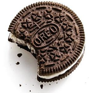 A single Oreo with a bite taken out of it.