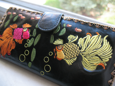 Front view of a black faux-leather wallet with colorful embroidered fish.