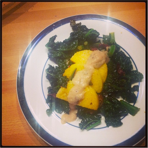 Instagram photo of a bed of kale and sun-dried tomatoes with half-moon polenta pieces topped with a white bean puree.