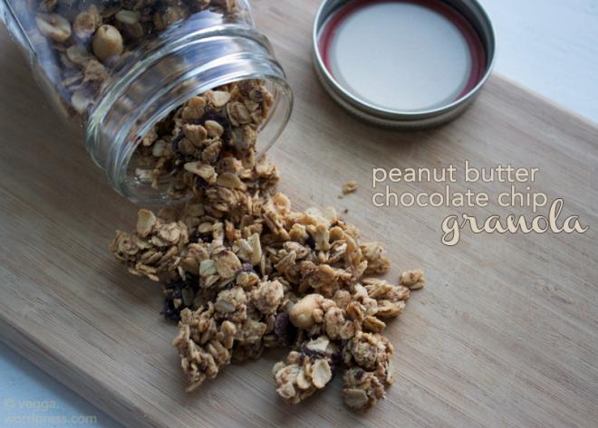 Peanut butter granola spilling from a mason jar onto a wooden cutting board.
