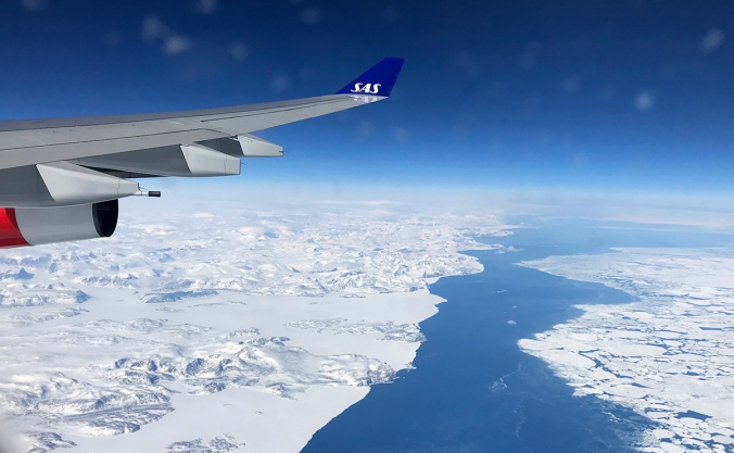SAS airline plane wing over a snowy and icy landscape
