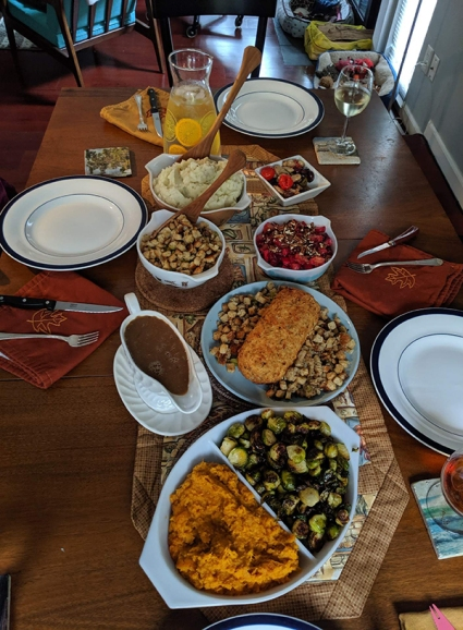 A slightly skewed top-down view of a kitchen table loaded with food and plates.