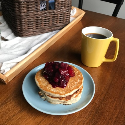 A small blue plate with a stack of pancakes, topped with a deep red fruit compote.