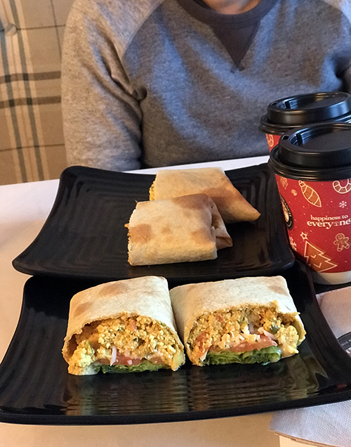 Straight-on shot of a wrap filled with tofu scramble, tomato, and lettuce.
