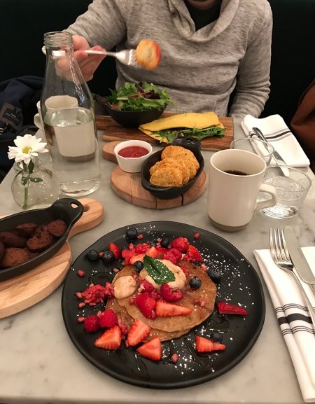 A white marble table piled with a plate of pancakes, a tureen of sliced sausages, a bowl of hash browns, and a plate with an omelette on it.