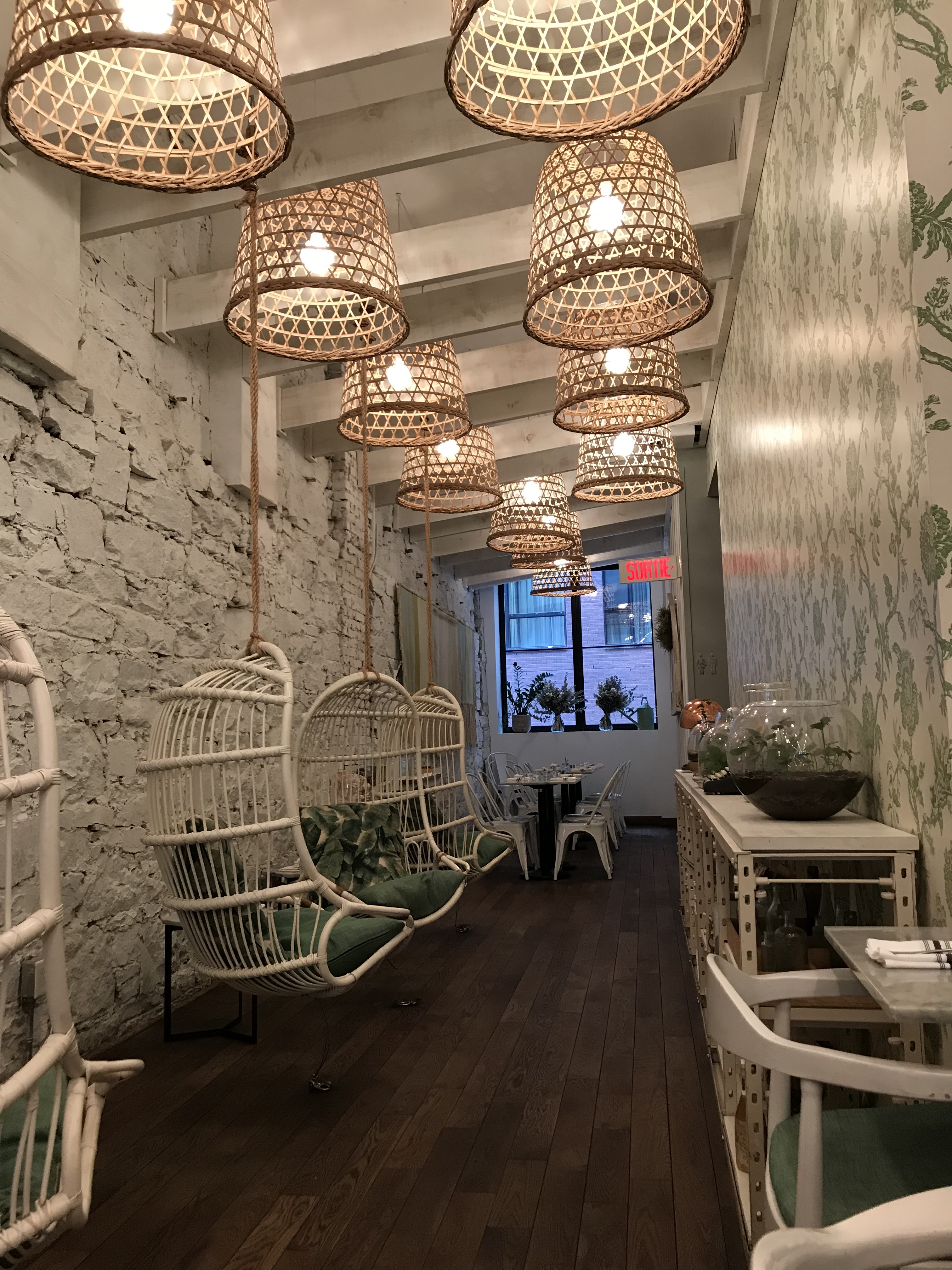 The interior of Lov, with whitewashed brick walls, hanging wicker chairs, and rattan light fixtures.