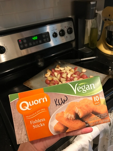 "In the foreground: a box of Quorn fishless sticks with the word ""Vegan"" quite large across the top. In the background: a sheet pan filled with raw chopped potatoes."