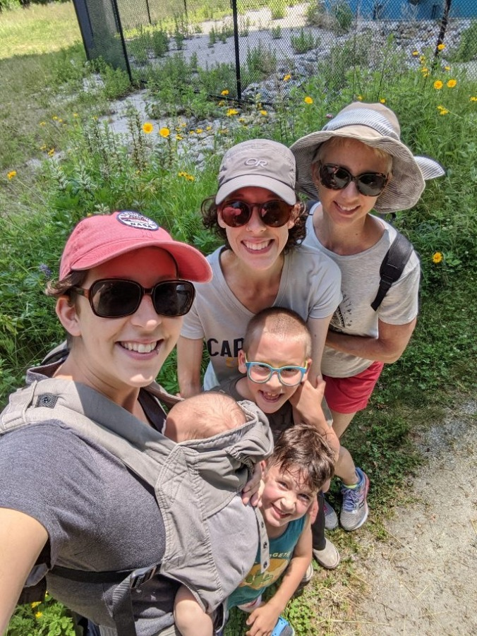 A top-down long-arm selfie of two young women, one middle-aged woman, two young kids, and a baby in a front pack.